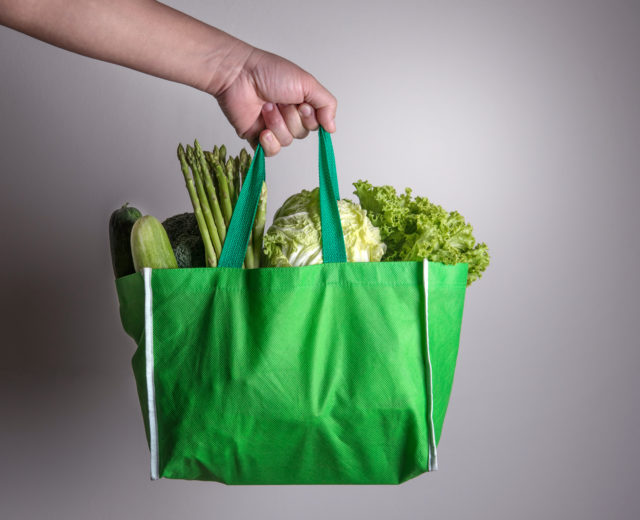 Green reusable bag with vegetables inside