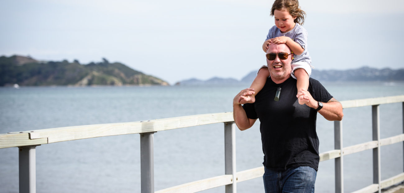 Man walking on wharf with child on shoulders