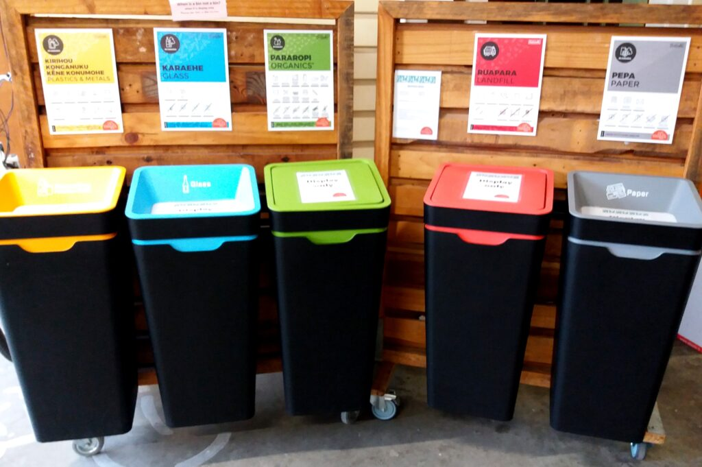recycling bins of different colours but same size lined up with explanatory signs on top of them