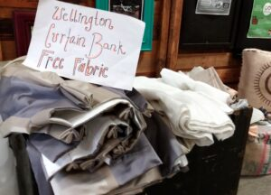 Box full of fabric scraps with a sign: Wellington Curtain Bank Free Fabric