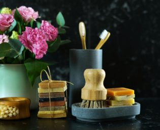 waste-free bathroom items such as soap bars, bamboo toothbrushes and brushes, flowers against a dark background