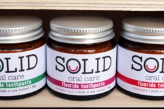 Solid oral care toothpaste in jars on a wooden shelf
